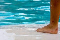 关闭孩子的一只受伤的脚在蓝色的游泳池边关于 库存图片