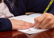 关闭孩子` s在纸的手文字,在木桌上的文字杂乱算术在屋子,学生儿童女孩做家庭作业的候宰栏里在 免版税库存图片