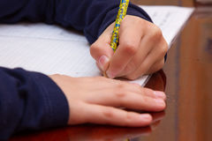 关闭孩子` s在纸的手文字,在木桌上的文字杂乱算术在屋子,学生儿童女孩做家庭作业的候宰栏里在 库存图片