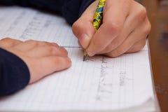 关闭孩子` s在纸的手文字,在木桌上的文字杂乱算术在屋子,学生儿童女孩做家庭作业的候宰栏里在 库存照片