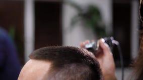 关闭客户的女性理发师切口头发末端的男性头和手使用梳子和特别hairclipper的 人 股票录像