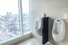 关闭室内尿壶人公共厕所,休息室行  有曲线现代设计尿壶碗的白色陶瓷尿壶在人棒 免版税库存图片
