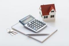 关闭家庭模型、计算器和笔记本 免版税库存照片