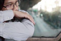 关闭对工作失望或用尽的沮丧的被注重的年轻亚洲商人感觉在有拷贝空间的外部办公室 免版税库存照片