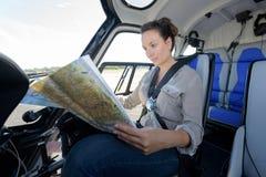 关闭射击俏丽的直升机飞行员读书地图 图库摄影