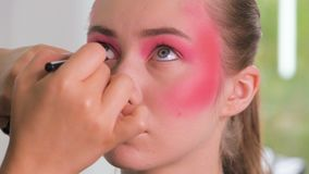 关闭射击 应用眼线膏的专业化妆师在模型的整个眼睛附近在绝尘室 beauvoir 股票视频