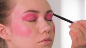 关闭射击 应用眼线膏的专业化妆师在模型的整个眼睛附近在绝尘室 beauvoir 影视素材