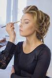 关闭射击 应用眼影膏的专业化妆师 库存图片