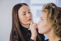 关闭射击 应用眼影膏的专业化妆师 库存照片