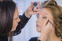 关闭射击 应用眼影膏的专业化妆师 免版税库存照片