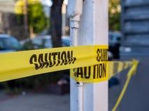 关闭小心垂悬在杆和拦住道路的黄色陷井 库存图片