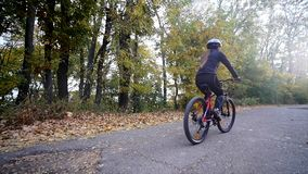 关闭少妇射击一辆自行车的在秋天公园 慢的行动 免版税库存图片