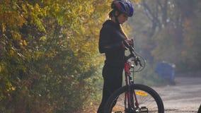 关闭少妇射击一辆自行车的在秋天公园 慢的行动 免版税库存照片
