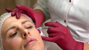 关闭少妇面孔有透明质酸射入由化妆师在美容院 股票视频