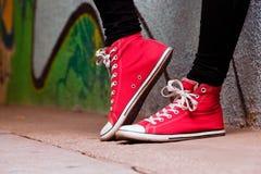 关闭少年佩带的红色运动鞋。 库存图片