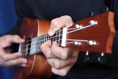 关闭尤克里里琴在音乐家手上,左手视图 图库摄影