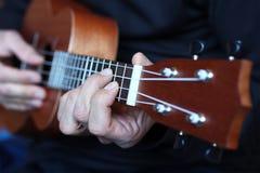 关闭尤克里里琴在音乐家手上 免版税库存照片