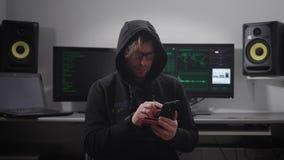 关闭展开对银行网络的一位戴头巾黑客网络攻击在智能手机帮助下在他的手上 黑色的人 影视素材