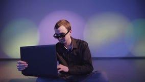 关闭工作在便携式计算机的年轻商人在轻音乐下 股票录像