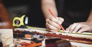 关闭工作在木材加工车间的木匠 做线 免版税库存图片