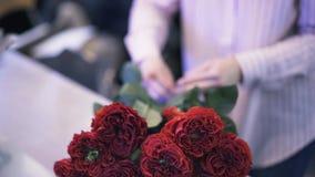 关闭工作在花店的妇女栓一束深红玫瑰 股票视频