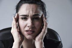 关闭工作在遭受强烈的头疼的重音的办公室的可爱的女商人 库存照片
