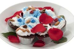 关闭巧克力杯形蛋糕的图象与玫瑰花瓣的在白色p 免版税库存照片