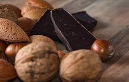 关闭巧克力被分类的坚果和pices在一个木选项的 库存照片