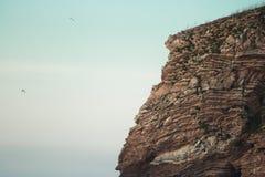 关闭巨大的在日落天空, hendaye的峭壁岩石被腐蚀的纹理 免版税库存照片