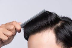 关闭干净的健康人` s头发照片  年轻人梳子他的h 库存照片