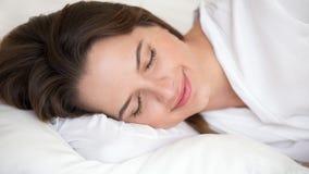关闭平安地睡觉在床上的镇静美丽的女孩 图库摄影