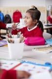 关闭年轻中国女小学生佩带的校服坐在一张书桌的在一间幼儿学校教室,选择聚焦,vert 库存照片