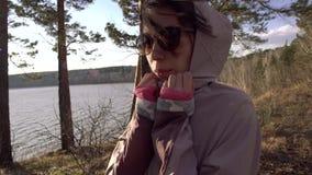 关闭年轻亚裔与吹在风的头发的妇女远足者探索的自然画象  迁徙在寒冷的远足者女孩 影视素材