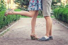 关闭年轻人和妇女的腿在一个浪漫日期期间在一个绿色庭院里 免版税库存照片