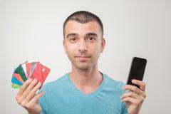 关闭年轻人画象拿着很多gredit卡片的玻璃的 免版税库存照片