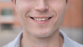 关闭年轻人的微笑的嘴唇和牙