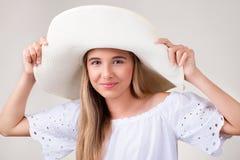 关闭年轻俏丽的女孩画象有白色帽子的 库存照片