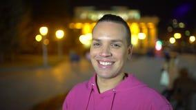 关闭年轻时髦的人画象戴眼镜的在市中心在晚上时间 微笑对照相机的年轻人 影视素材