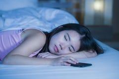 关闭年轻甜和美丽的亚裔中国妇女睡觉在床上的20s或30s画象在她的手机旁边在互联网 库存图片