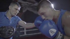 关闭年轻男性拳击手战斗机运动员个人教练实践的锻炼训练拳打勾子脚踢拳击圆环射击  股票视频