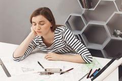 关闭年轻美丽的困自由职业者的建筑师女孩对负顶头用手,睡着,当准备时 免版税库存照片