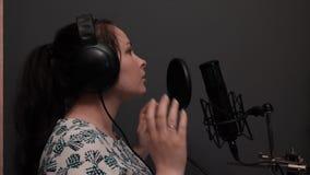 关闭年轻美女录音歌在有灰色墙壁的专业演播室 影视素材