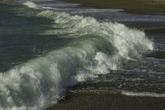 关闭庄严撞入一个黑暗的pebbled海滩的urquoise和鲜绿色的针对性的膨胀在一个天空蔚蓝夏日在西西里岛 库存照片