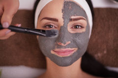 关闭应用面部面具的手于妇女面孔在美容院 免版税库存图片