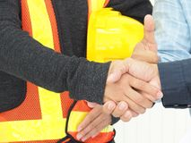 关闭建筑工人和工程师握手,当工作在办公室中心时 免版税图库摄影