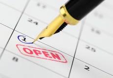 关闭开放在日历的邮票和钢笔 库存照片