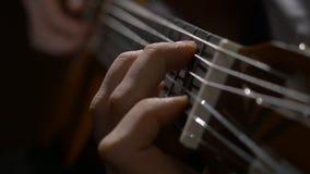 关闭弹声学吉他的吉他弹奏者手 关闭一个人的射击有他的手指的在吉他的苦恼 免版税库存图片
