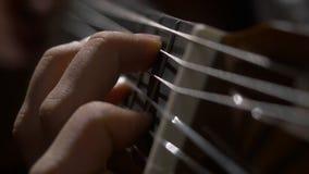 关闭弹声学吉他的吉他弹奏者手 关闭一个人的射击有他的手指的在吉他的苦恼 库存图片
