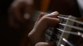 关闭弹声学吉他的吉他弹奏者手 关闭一个人的射击有他的手指的在吉他的苦恼 库存照片