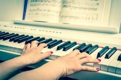 关闭弹钢琴的一个少妇的手 免版税库存图片
